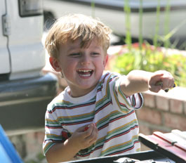 smiling boy playing with toy race cars at party